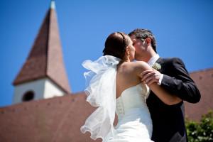 Trauung - Brautpaar küsst sich vor einer Kirche